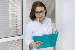 Retrato de la enfermera de sexo femenino adulta, mujer con el tablero, trabajando en hospital fotografía de archivo