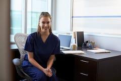 Retrato de la enfermera Wearing Scrubs Sitting en el escritorio en oficina Fotografía de archivo