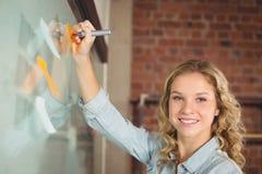 Retrato de la escritura de la empresaria en notas pegajosas en oficina Foto de archivo libre de regalías