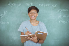 Retrato de la escritura del colegial en cuaderno contra la pizarra en sala de clase Foto de archivo libre de regalías