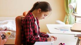 Retrato de la escritura hermosa de la muchacha en cuaderno detrás del escritorio en el dormitorio Fotografía de archivo libre de regalías