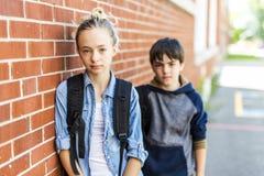 Retrato de la escuela 10 años de muchacho y muchacha que se divierten afuera Imagen de archivo libre de regalías