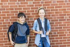 Retrato de la escuela 10 años de muchacho y muchacha que se divierten afuera Imagenes de archivo