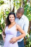 Retrato de la esposa embarazada feliz con el vientre conmovedor del marido Foto de archivo