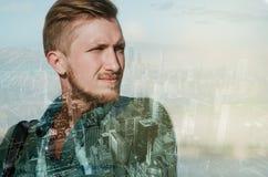 Retrato de la exposición doble del hombre barbudo joven de la cara que piensa en ciudad grande Sueño y concepto del éxito, megaló Foto de archivo