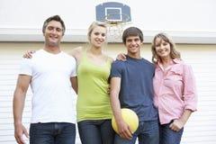 Retrato de la familia adolescente que juega a baloncesto fuera del garaje Fotografía de archivo