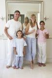 Retrato de la familia alrededor para cepillar los dientes en espejo del cuarto de baño Fotografía de archivo