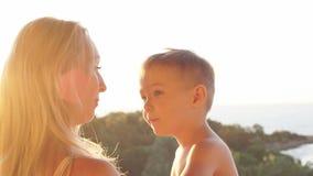 Retrato de la familia caucásica feliz en la puesta del sol Madre e hijo de risa en puesta del sol Cámara lenta almacen de video