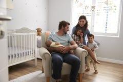 Retrato de la familia con los niños y el hijo recién nacido en cuarto de niños foto de archivo