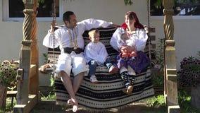 Retrato de la familia con ropa tradicional en el oscilación de madera, día de fiesta rural, madre y padre joven, niño divertido y almacen de video