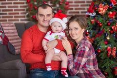 Retrato de la familia de la feliz Navidad La sonrisa Parents con la hija del bebé en casa que celebra Año Nuevo Árbol de navidad Imágenes de archivo libres de regalías