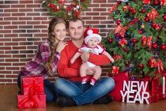 Retrato de la familia de la feliz Navidad La sonrisa Parents con la hija del bebé en casa que celebra Año Nuevo Árbol de navidad Imagen de archivo libre de regalías