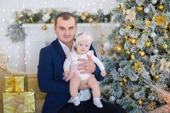 Retrato de la familia de la feliz Navidad La sonrisa Parents con la hija del bebé en casa que celebra Año Nuevo Árbol de navidad Fotos de archivo