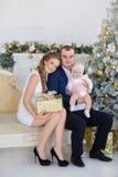 Retrato de la familia de la feliz Navidad La sonrisa Parents con la hija del bebé en casa que celebra Año Nuevo Árbol de navidad Foto de archivo libre de regalías