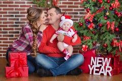 Retrato de la familia de la feliz Navidad La sonrisa Parents con la hija del bebé en casa que celebra Año Nuevo Árbol de navidad Imagenes de archivo