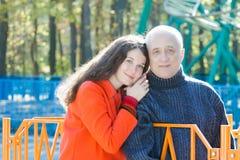 Retrato de la familia de la hija adulta de abarcamiento y de su padre mayor en el fondo del parque de atracciones de la montaña r Fotos de archivo
