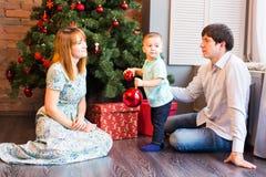 Retrato de la familia de la Navidad en la sala de estar casera del día de fiesta, casa que adorna por el árbol de Navidad Fotografía de archivo libre de regalías