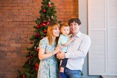 Retrato de la familia de la Navidad en la sala de estar casera del día de fiesta, casa que adorna por el árbol de Navidad Imagenes de archivo