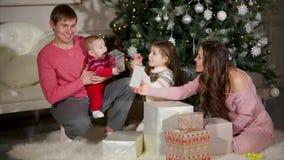 Retrato de la familia debajo de un árbol de navidad almacen de metraje de vídeo