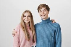Retrato de la familia del hermano y de la hermana contra fondo gris El hombre de pelo rubio del inconformista joven se vistió en  fotos de archivo
