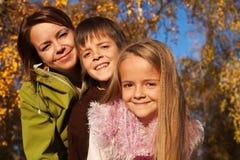 Retrato de la familia del otoño en el bosque soleado Imágenes de archivo libres de regalías