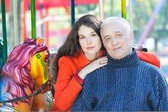 Retrato de la familia del parque de atracciones de la hija adulta de abarcamiento y del padre mayor Imagen de archivo