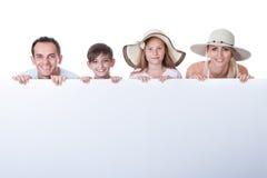 Retrato de la familia detrás de la tarjeta en blanco Imágenes de archivo libres de regalías