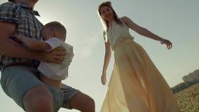 Retrato de la familia emocionada joven que se divierte en un día soleado Engendre los tiros su niño en el aire y lo coge almacen de metraje de vídeo