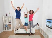 Retrato de la familia emocionada que salta en casa Foto de archivo