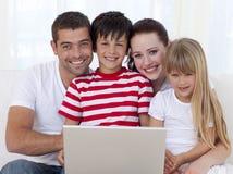 Retrato de la familia en el país usando una computadora portátil Imágenes de archivo libres de regalías