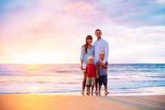 Retrato de la familia en la playa en la puesta del sol Foto de archivo libre de regalías
