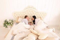 Retrato de la familia en pijamas en cama y ofensa de la charla imagenes de archivo