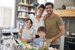 Retrato de la familia en receta de siguiente de la cocina en la tableta de Digitaces Imagenes de archivo