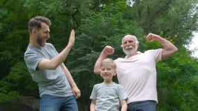 Retrato de la familia feliz - abuelo, padre y su hijo sonriendo y mostrando sus músculos al aire libre en parque en fondo metrajes