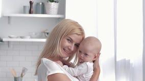 Retrato de la familia feliz en casa, del nuevo abrazo de la madre y de la muchacha recién nacida de los besos en cocina metrajes