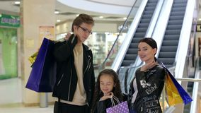 Retrato de la familia feliz en centro comercial con los paquetes de las compras cerca de la escalera móvil almacen de metraje de vídeo