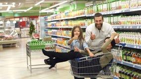 Retrato de la familia feliz en el supermercado, mamá de la diversión que se sienta en el carro del ultramarinos almacen de video