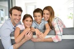 Retrato de la familia feliz en la risa del sofá Imagen de archivo