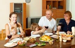 Retrato de la familia feliz junto sobre la mesa de comedor que come el polluelo fotos de archivo libres de regalías