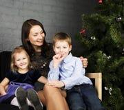 Retrato de la familia feliz, madre con los niños que asientan cerca del árbol de navidad, concepto de la gente de la forma de vid Fotos de archivo