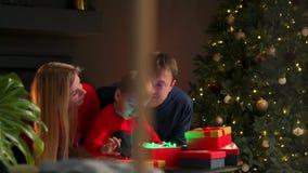 Retrato de la familia feliz que abre una caja de regalo del regalo de Navidad por la tarde Concepto de días de fiesta, sorpresa,  almacen de metraje de vídeo