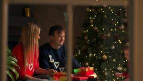 Retrato de la familia feliz que abre una caja de regalo del regalo de Navidad por la tarde Concepto de días de fiesta, sorpresa,  almacen de video