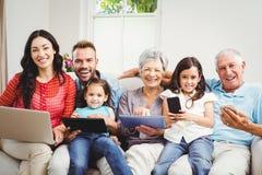 Retrato de la familia feliz que lleva a cabo tecnologías en casa foto de archivo