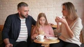 Retrato de la familia feliz que pasa el tiempo junto en café Se divierten mucho que hablan el uno al otro metrajes