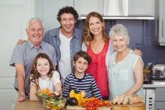 Retrato de la familia feliz que se coloca en cocina Foto de archivo