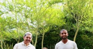 Retrato de la familia feliz que se coloca en el parque 4k metrajes