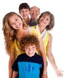 Retrato de la familia feliz que se coloca en una fila Imagenes de archivo