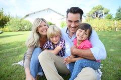 Retrato de la familia feliz que se sienta en hierba foto de archivo