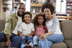 Retrato de la familia feliz que se sienta en Sofa In Open Plan Lounge imágenes de archivo libres de regalías