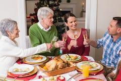 Retrato de la familia feliz que tuesta en la cena de la Navidad Imagen de archivo libre de regalías